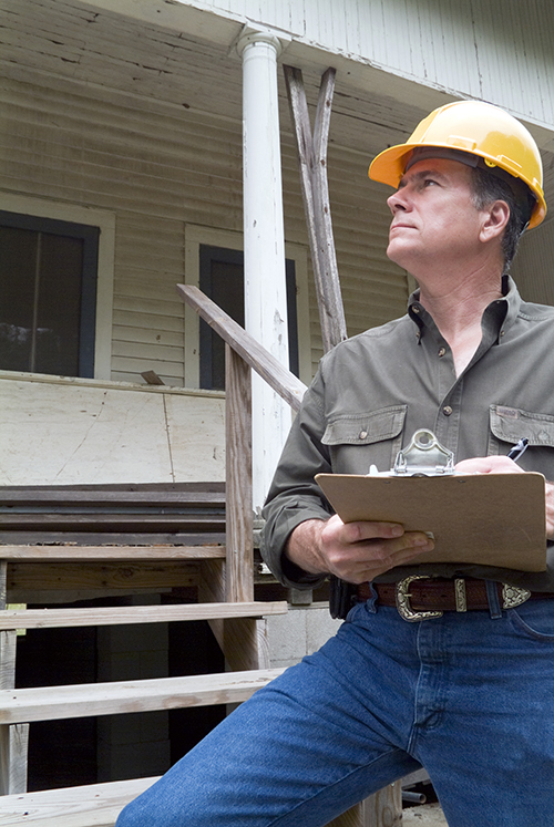 A man in a hard hat standing in front of an old rundown house holding a clipboard in his hand.