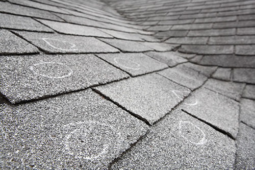 Old roof with hail damage, chalk circles mark the damage